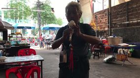 KO CHANG, THAILAND - APRIL 9, 2018: Man playing flute at a cheap thay restaurant terrace stock footage