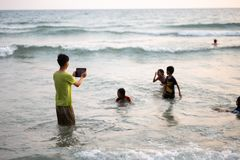 KO CHANG, THAILAND - APRIL 10, 2018: Thay asian children playing in sea - Boy takes photo via a tablet royalty free stock images