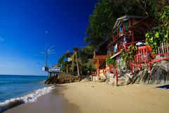 KO CHANG, THAILAND - DECEMBER 7. 2018: View on white sand beach with green trees and colorful wood houses stock image