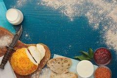 Koźli ser z szafranem, chlebem i mlekiem na turkusowym tle, zdjęcie royalty free