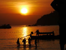 Ko Lipe, Thailand. Sunset on the main beach of the Thai island of Koh Lipe, looking out to sea, with silhouettes of tourists, and traditional boats Royalty Free Stock Images