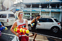 KO SAMUI, THAILAND - APRIL 13: Unidentified man shooting water at other people in a water fight festival or Songkran Festival Stock Photo
