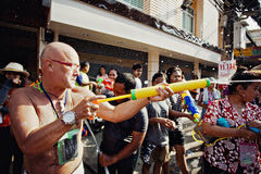 KO SAMUI, THAILAND - APRIL 13: Unidentified man shooting water at other people in a water fight festival or Songkran Festival Royalty Free Stock Image