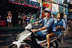 KO SAMUI, THAILAND - APRIL 13: Unidentified thai people on a bike on Songkran Festival (Thai New Year). On April 13, 2014 in Chaweng Main Road, Ko Samui island Royalty Free Stock Photo