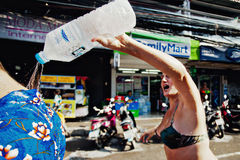 KO SAMUI, THAILAND - APRIL 13:  Unidentified woman pouring ice water by the collar on Songkran Festival Royalty Free Stock Photography