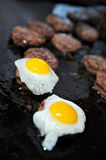 Kobe beef Sliders topped with quail egg. Several mini Kobe beef burgers cooking on a grill.  Two are topped with a fresh fried quail egg Royalty Free Stock Photos