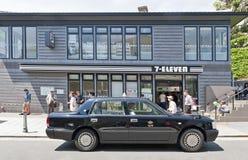 Kobe, Giappone - aprile 2016: la facciata 7-Eleven nella progettazione nera di tema con un taxi nero si è fermata nella parte ant Fotografie Stock