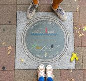 Female and Men legs standing in front of a beautifully decorated Manhole of Kobe City, Japan stock image