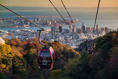 Kobe Ropeway with skyline cityscape at sunset. Kobe, Japan - November 25, 2016: Shin-Kobe Ropeway cable cars to Nunobiki Herb Garden with autumn foliage color stock image
