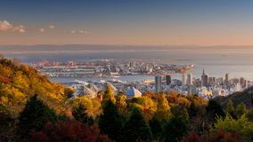 Kobe skyline cityscape during sunset, Japan. Top view cityscape from Nunobiki Herb Garden in aun foliage colors with skyline urban view and Kobe port during stock photo