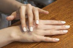 Kobiece ręki stosują śmietankę na skórze Obraz Royalty Free