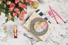 Kobiecy miejsca pracy pojęcie Freelance workspace w mieszkanie nieatutowym stylu z cukierkami, kwiaty, notatniki na bielu wykłada Obraz Royalty Free