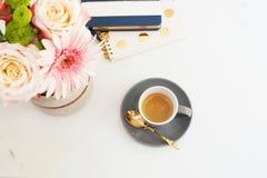Kobiecy miejsca pracy pojęcie w mieszkanie nieatutowym stylu z kawą, kwiaty, notatniki na bielu wykłada marmurem tło Odgórny wido fotografia royalty free