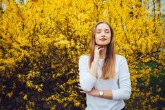 Kobiet agains possing żółty kwitnący drzewo Mimozy drzewa kwitnienie Obrazy Stock