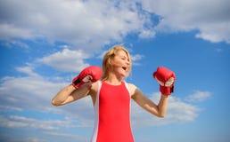 Kobiet bokserskich rękawiczek silna podwyżka wręcza niebieskiego nieba tło Dziewczyn bokserskich rękawiczek symbolu walka dla kob zdjęcia royalty free