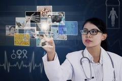 Kobiet doktorskie wzruszające fotografie na błękitnym ekranie sensorowym obraz stock