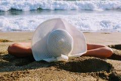Kobiet kłamstwa na piasku przeciw tłu denna kipiel w białym kapeluszu z szerokim rondem Zdjęcia Stock