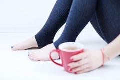 Kobiet nogi i filiżanka herbata Zdjęcie Royalty Free