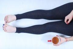 Kobiet nogi i filiżanka herbata Obrazy Stock