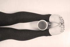Kobiet nogi i filiżanka herbata Fotografia Stock