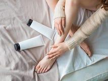 Kobiet nogi i tubka moisturiser na łóżku Skóry opieki pojęcie obrazy stock