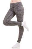 Kobiet nogi od strony stoi na jeden nodze z inną nogą podnoszącą w białych skarpetach w popielatych sportów termicznych spodniach Zdjęcie Royalty Free