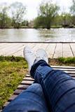 Kobiet nogi w cajgach i białych sneakers kłamają na deckchair fotografia stock