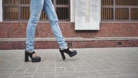 Kobiet nogi w czarnych platforma butach, niebieskich dżinsach chodzi w miasto ulicie i zbiory