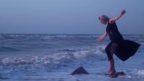 Kobiet próby utrzymują jej równowagę, stoi na kamieniu na jeden nodze w morzu, spadki, śmiechy zbiory