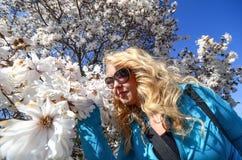 Kobiet przerwy wąchać pięknego białego kwiatu kwitną na drzewie podczas wiosny zdjęcie stock