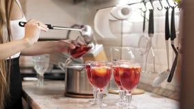 Kobiet ręki nalewa rozmyślającego wino w szkła przy przyjęciem zbiory