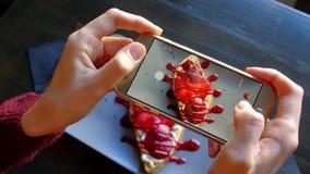 Kobiet ręki używa smartphone biorą fotografię piękny apetyczny deser zbiory