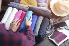 Kobiet ręk paczka odziewa w walizki torbie na łóżku, przygotowywa dla tęsknić weekend, nowej podróży i podróży obraz royalty free