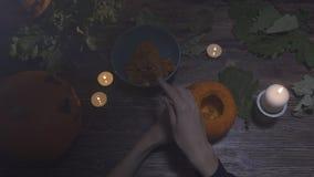 Kobiet ręki łyżkuje out ziarna i zawartość bania na drewnianym stole z świeczkami przy nocą Halloweenowy temat, dźwigarka zdjęcie wideo