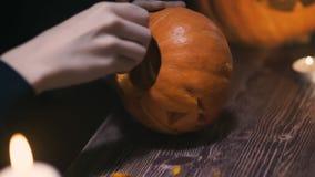 Kobiet ręki łyżkuje out ziarna i zawartość bania na drewnianym stole z świeczkami przy nocą Halloweenowy temat, dźwigarka zbiory