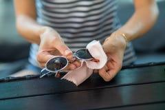 Kobiet ręki czyści słońc szkła i wyciera z mikro włókna wytarciem zdjęcie stock