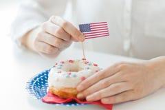 Kobiet ręki dekoruje pączek z flaga amerykańską fotografia stock