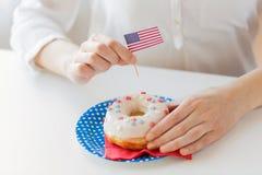 Kobiet ręki dekoruje pączek z flaga amerykańską obrazy royalty free