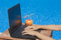 Kobiet ręki na laptop klawiaturze przy poolside obrazy stock