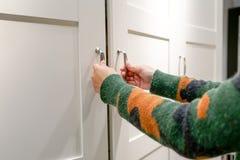 Kobiet ręki otwierają spiżarnię, gabinetowego drzwi/, biały drewniany drzwi Obrazy Royalty Free