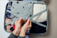 Kobiet ręki pakować odziewają w walizce Zima wakacje i hol Obraz Stock
