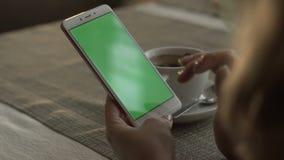 Kobiet ręki pisać na maszynie na zieleni ekranizują telefon komórkowego na tło filiżance zbiory