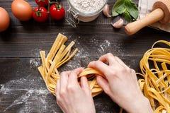 Kobiet ręki robi świeżemu domowej roboty makaronowi Makaronów składniki na ciemnym drewnianym stołowym odgórnym widoku Zdjęcia Stock