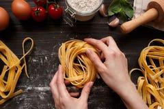 Kobiet ręki robi świeżemu domowej roboty makaronowi Makaronów składniki na ciemnym drewnianym stołowym odgórnym widoku Obrazy Royalty Free