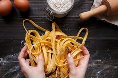 Kobiet ręki robi świeżemu domowej roboty makaronowi Makaronów składniki na ciemnym drewnianym stołowym odgórnym widoku Fotografia Stock
