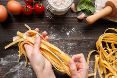 Kobiet ręki robi świeżemu domowej roboty makaronowi Makaronów składniki na ciemnym drewnianym stołowym odgórnym widoku Fotografia Royalty Free