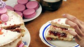 Kobiet ręki stawia na talerzu kawałek dekorującego tort z macaroons, pokrojonymi truskawkami i lilymi kwiatami, 4K zbiory