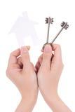 Kobiet ręki trzyma papier mieścą i klucze odizolowywający na bielu Zdjęcie Royalty Free