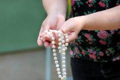 Kobiet ręki trzyma perełkowego koralika jewellery Zbliżenie żeńska ręka z perełkową biżuterią Żeńska ręka trzyma sznurek perła Fotografia Stock