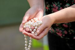 Kobiet ręki trzyma perełkowego koralika jewellery Zbliżenie żeńska ręka z perełkową biżuterią Żeńska ręka trzyma sznurek perła Obraz Royalty Free